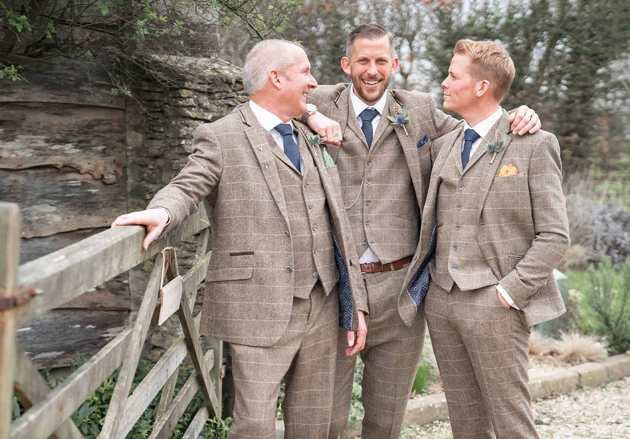 A groom and two best men pose for wedding photos at Tetbury wedding venue The Old Tythe Barn Tetbury.