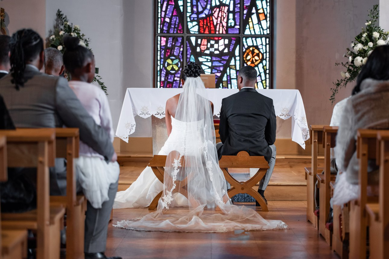 The bride and groom sit at the front of the Roman Catholic Church of Our Lady Queen of All Creation in Hemel Hempstead. The glorious and colourful stained glass window behind the altar brings colour into their wedding photo.