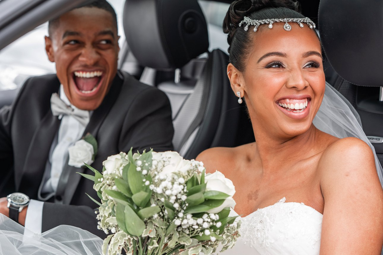 A beaming bride and groom in their car after their Hertfordshire marriage ceremony.