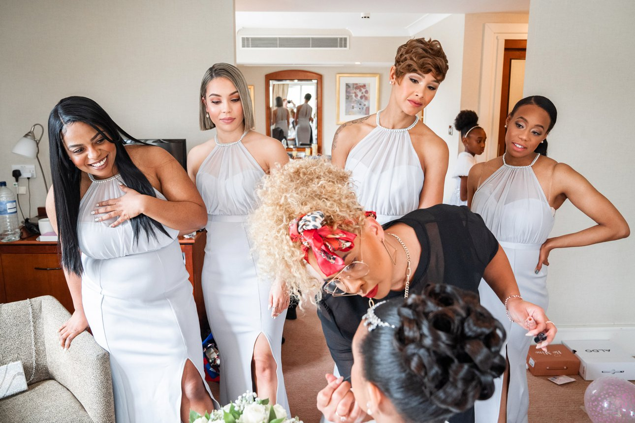 The bridesmaids watch the bride and her make-up artist Ariella Beauty at work before her Borehamwood wedding.