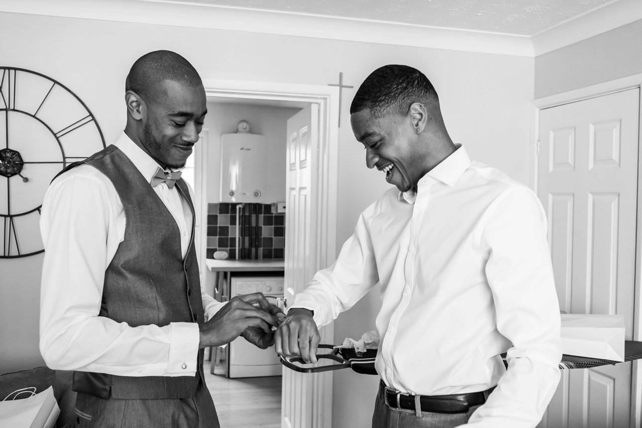 The groom and his best man help each other to get dressed for the groom's wedding at the Roman Catholilc Church of our Lady Queen of Creation.