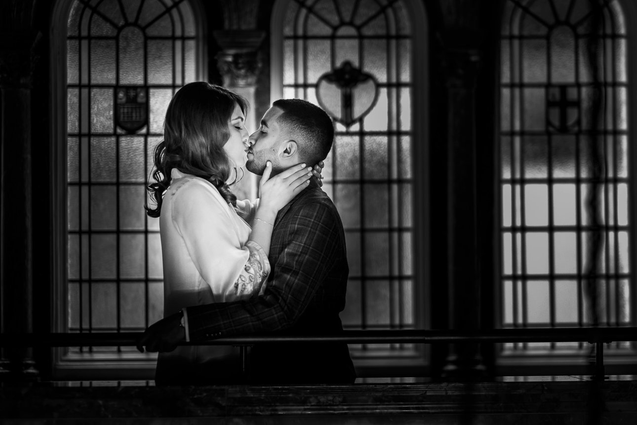 Black and white portrait of a bride and groom kissing.