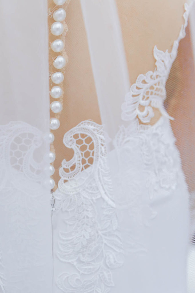 Lace and covered button details of a wedding dress and veil.