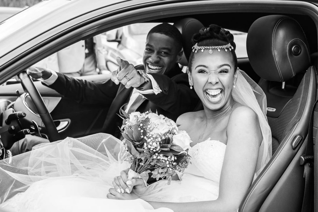 A bride and groom laugh in their car after the wedding ceremony.
