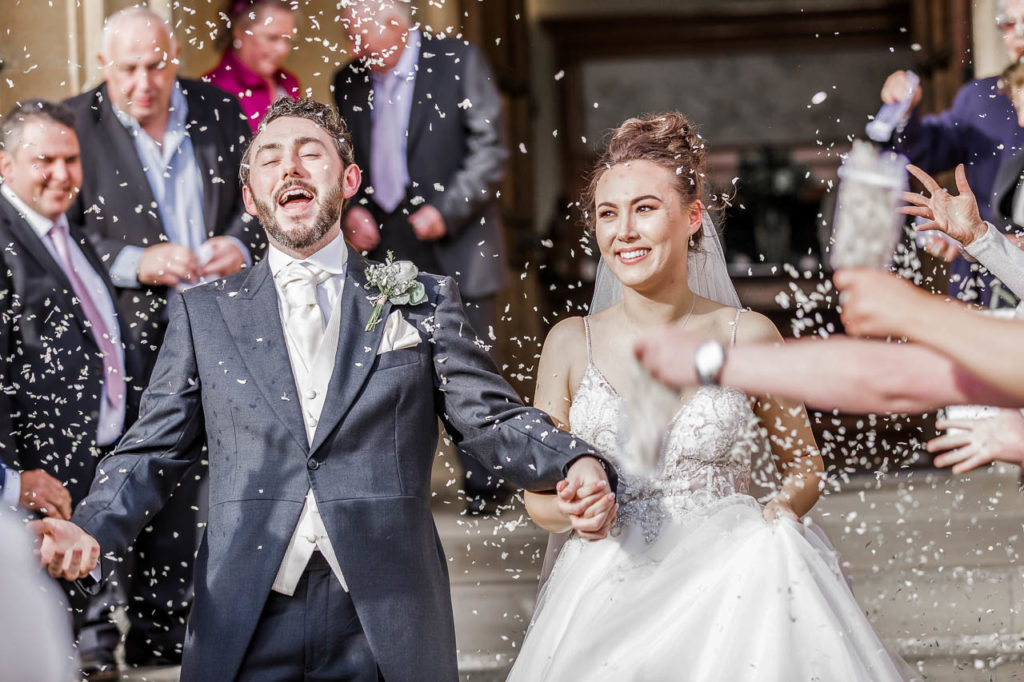 A bride and groom exit their ceremony in a whirl of confetti.