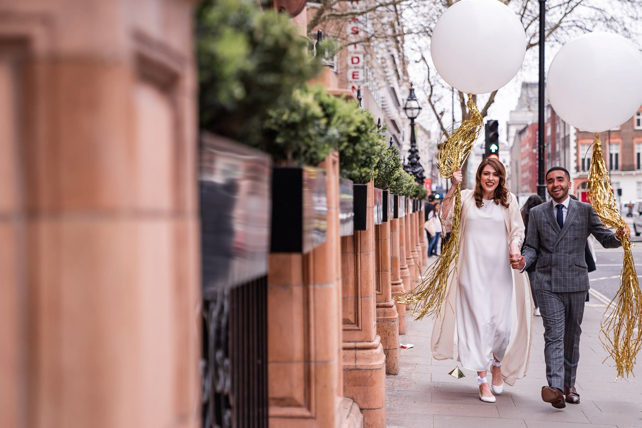 A bride and groom walk around Russell Square holding large spherical white balloons from their wedding.