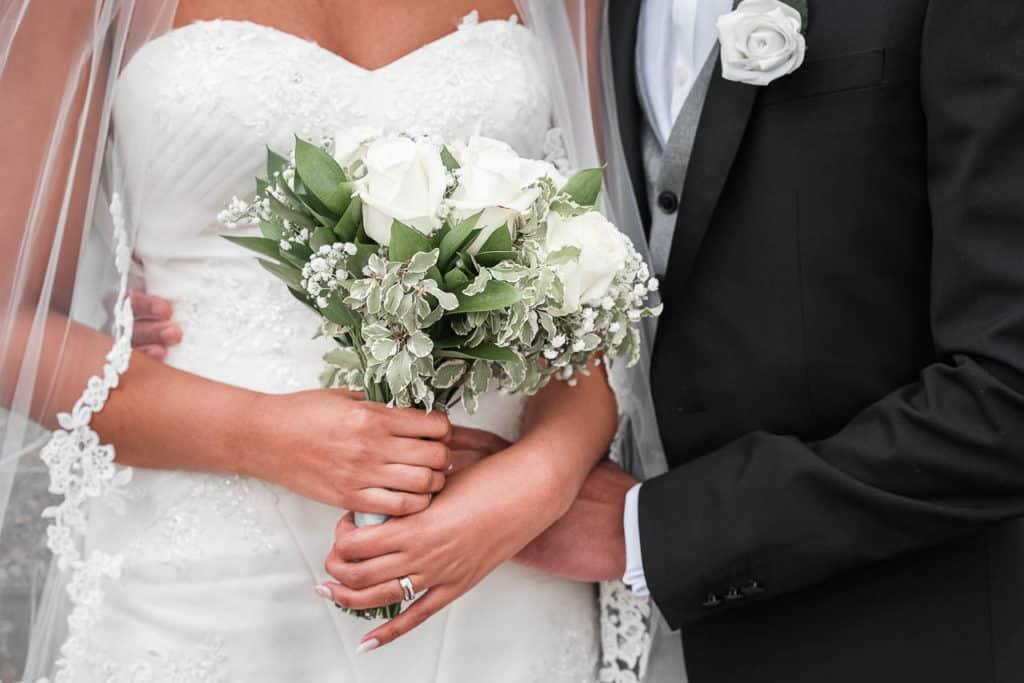 Details of a bride holding a bouquet alongside her groom.