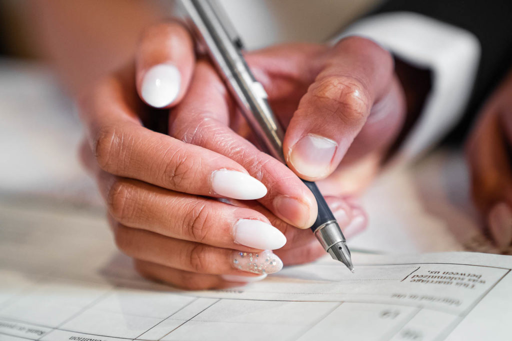 A bride and groom's hands as they sign the marriage register.