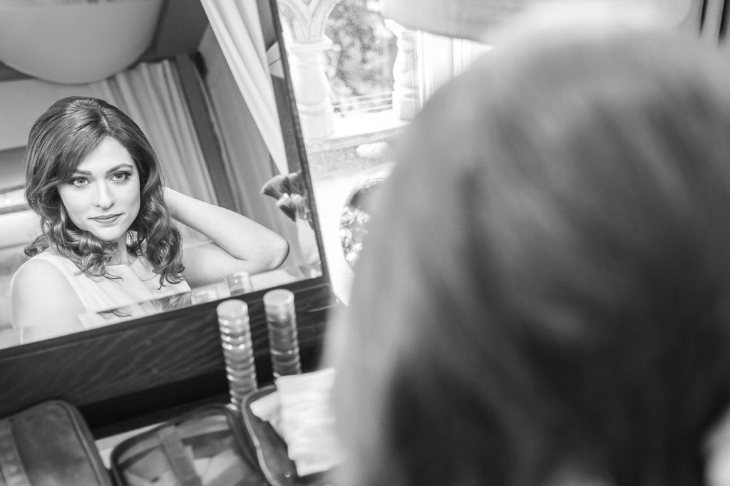 A bride sees herself in the mirror on her wedding morning after having her hair and make-up done professionally.