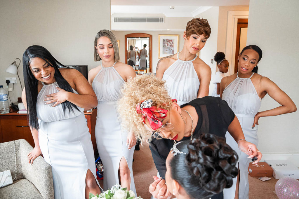 Bridesmaids watch their friend have her hair and make-up done on her wedding morning.