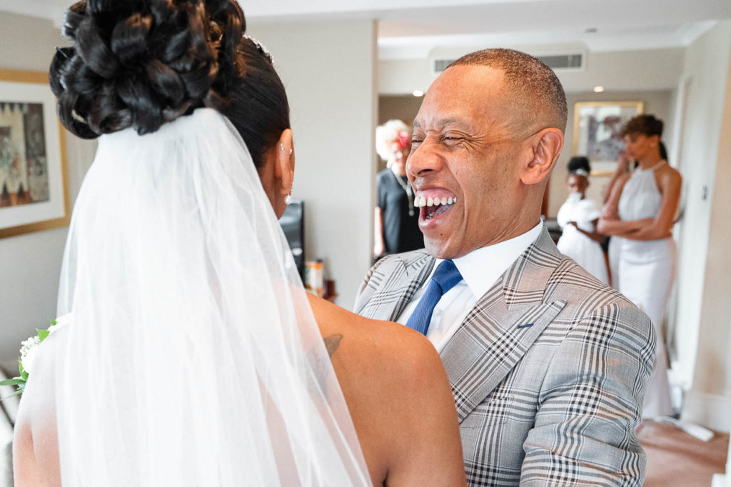 A father laughs and smiles at seeing his daughter as a bride for the first time.