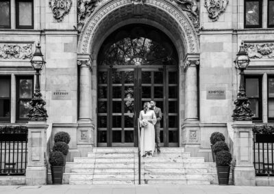 A bride and groom stand on the steps of the Kimpton Fitzroy London