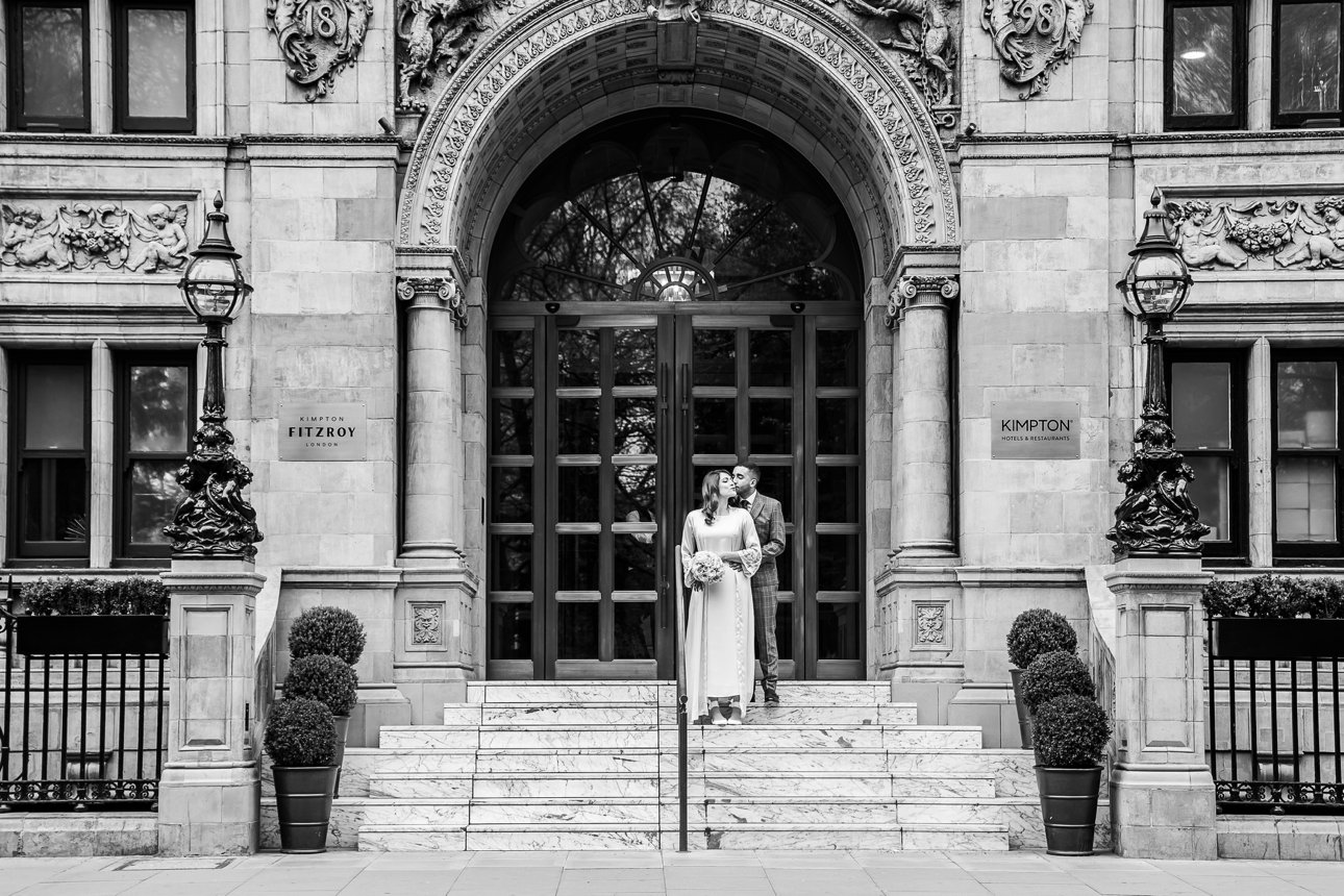 A bride and groom stand on the steps of the Kimpton Fitzroy London after their wedding ceremony inside.