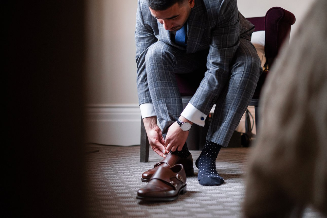 The groom puts on his Loake leather buckled shoes before his wedding ceremony.