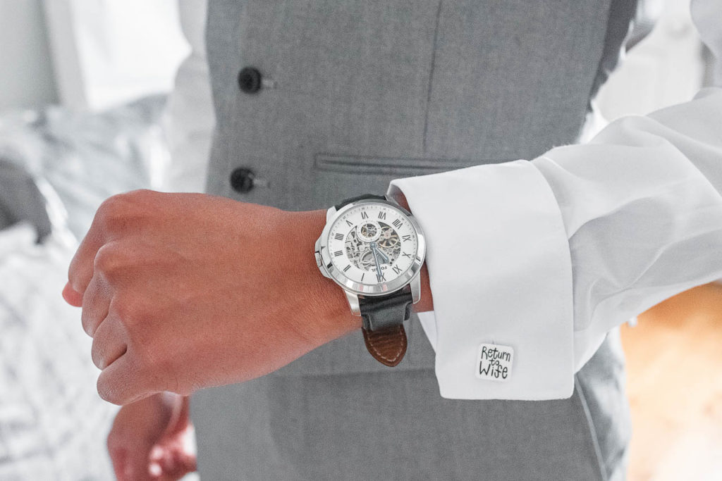 Wedding detail: a groom's watch and cufflinks in his white dress shirt.