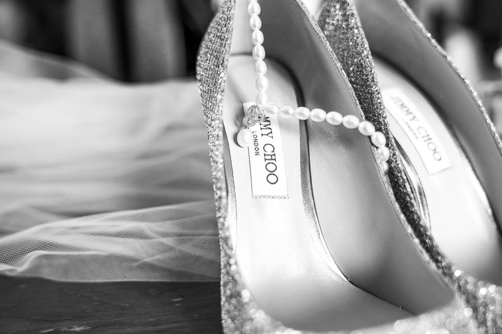 Jimmy Choo wedding shoes draped with a pearl necklace, ready for the bride.