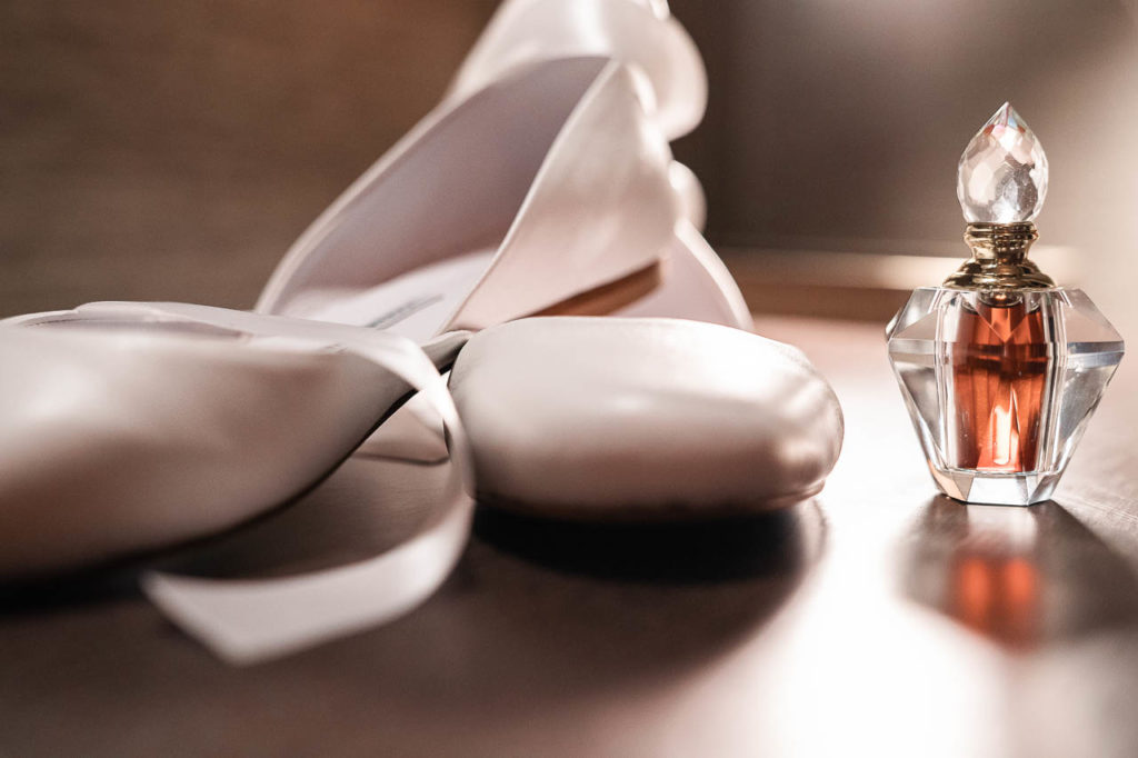 Stylish flat shoes for the bride - ribbons add a ballerina touch to the wedding shoes. The bride's perfume is another detail from the bridal preparations.