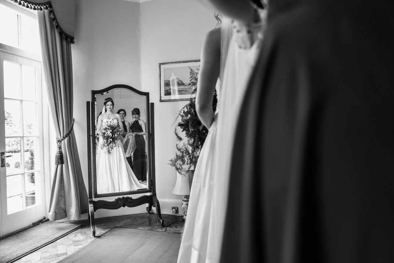 Essex bride Elisa looks in the mirror before her wedding at The Lawns, Rochford. Photographer: Natalie Chiverton