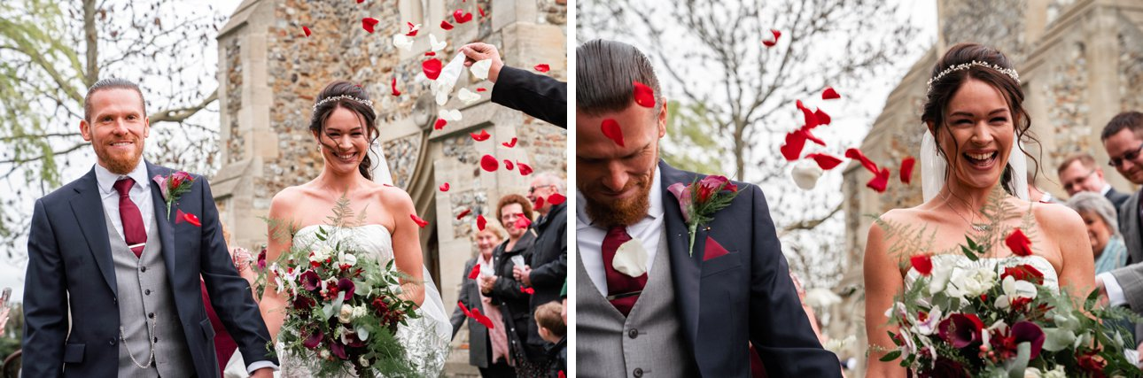 Red rose petal confetti showers over the bride and groom after their wedding at St Peter and St Paul's Hockley, in Essex.