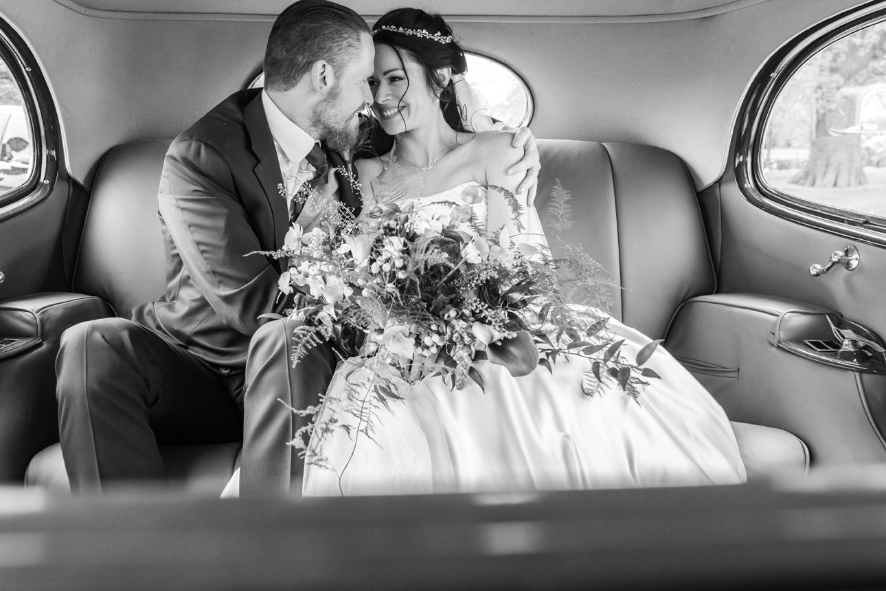 A bride and groom have a quiet moment in the back of their classic car after their wedding ceremony.