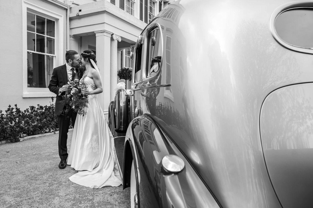 The bride and groom kiss near their classic car transport at The Lawn, Rochford.