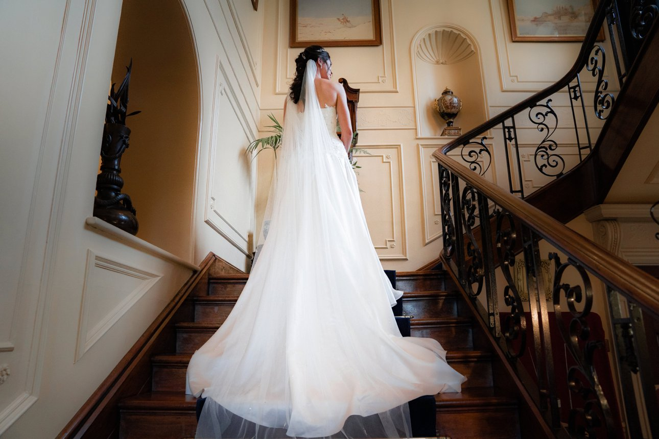 A photo of the back of the bride's dress on the great stairs at The Lawn Rochford in Essex.