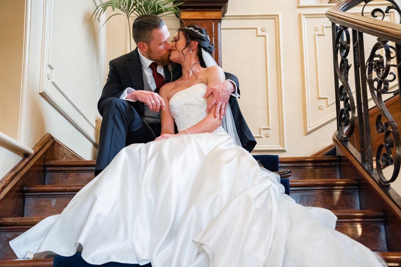 A bride and groom sit on the grand staircase at Essex wedding venue The Lawn.