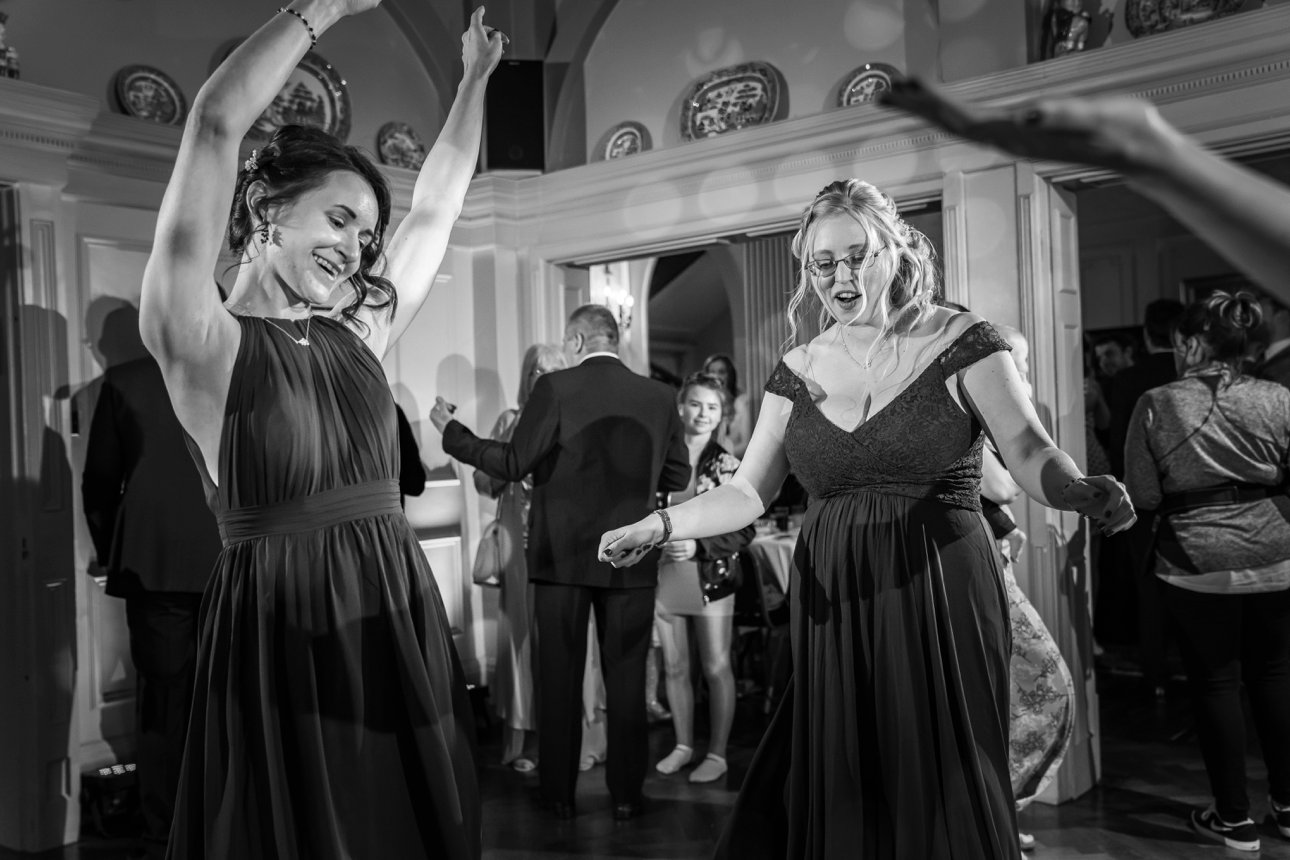 Black and white photo of bridesmaids boogying at a wedding at The Lawn, Rochford.