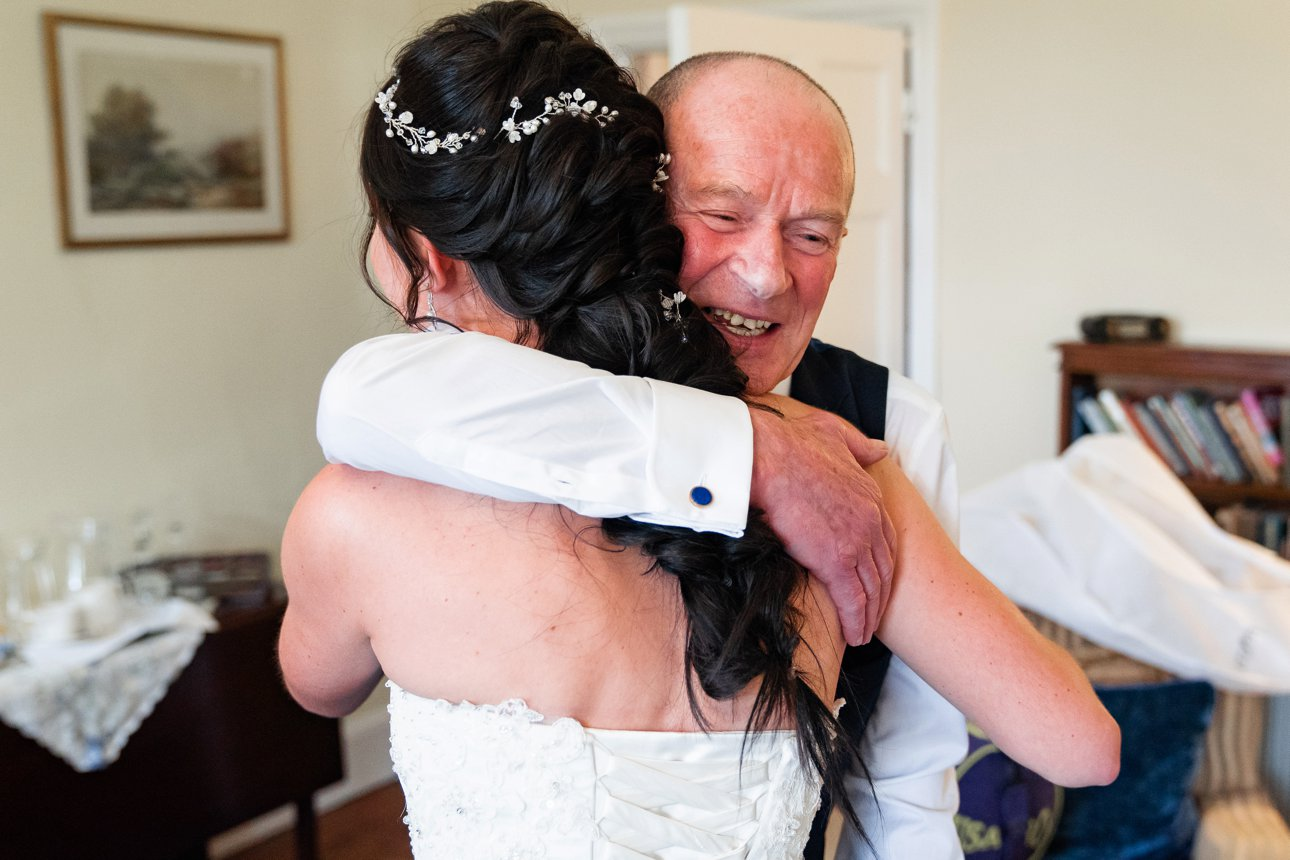 Father of bride hugs his daughter in her white dress at The Lawn - Essex wedding venue.