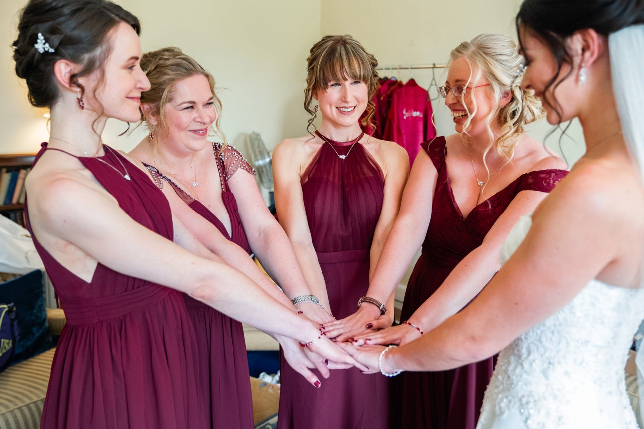 The bride and bridesmaids group when they are all ready for the wedding and reception. The bridesmaids are wearing deep red dresses.