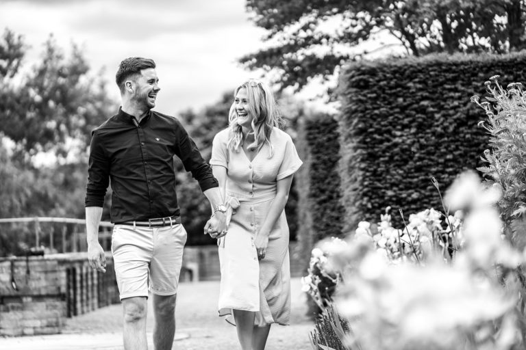 Couple portraits taken at The Grove at Chandlers Cross in Hertfordshire by local photographer Natalie Chiverton. The couple is walking through the grounds of The Grove laughing and joking, having fun.