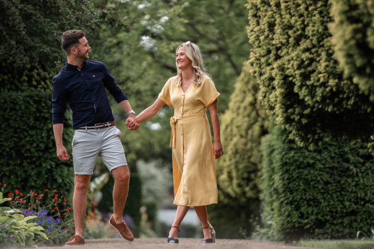 A summer engagement photo of a couple of teachers walking around the grounds of The Grove, in Hertfordshire.