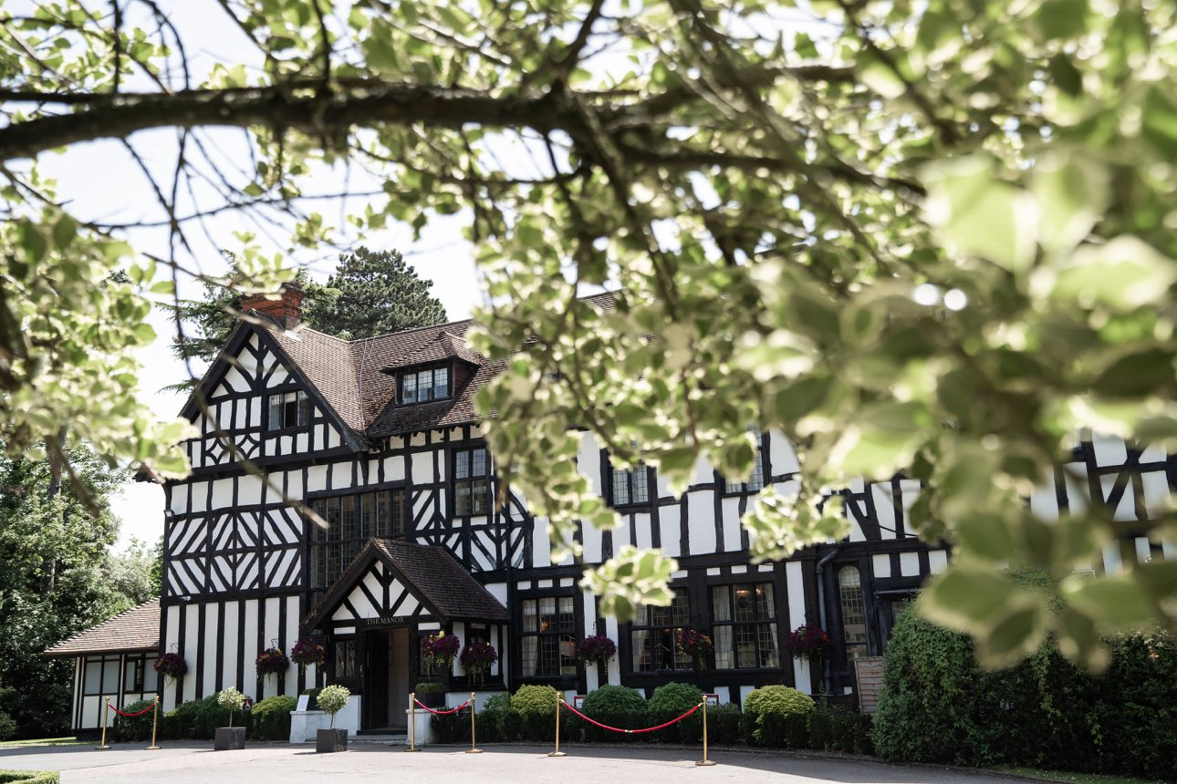 The Manor Elstree - Laura Ashley Hotel nestled behind a green branch in leafy Borehamwood, Hertfordshire.