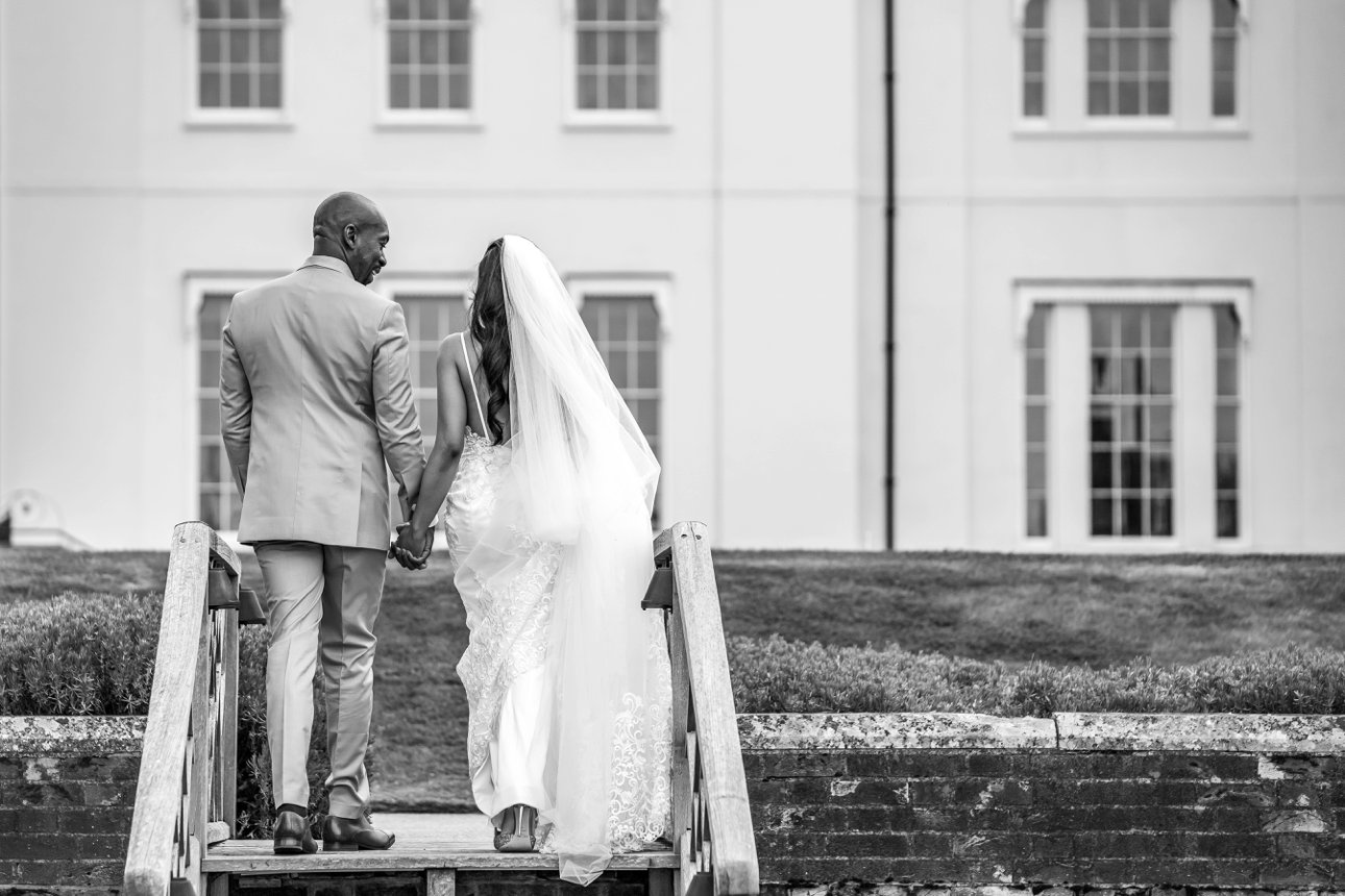 Black and white photo of the bride and groom at Coworth Park. The bride is wearing an Ashley and Justin Bridal white lace dress and cathedral length veil.