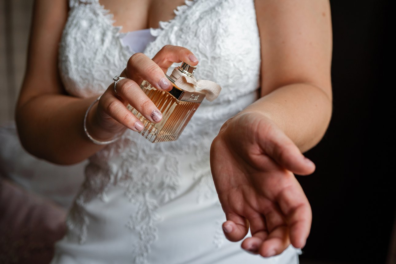 A bride sprays Chloe on her wrist on the morning of her wedding, ready to walk down the aisle at the Manor Elstree - A Laura Ashley hotel.