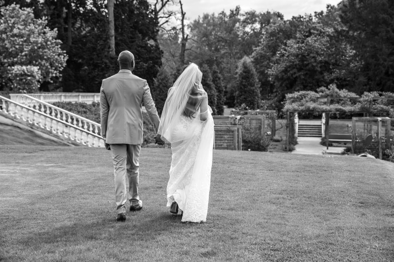 Coworth Park hosts the wedding of this bride and groom, pictured walking across the wedding venue's extensive lawns.
