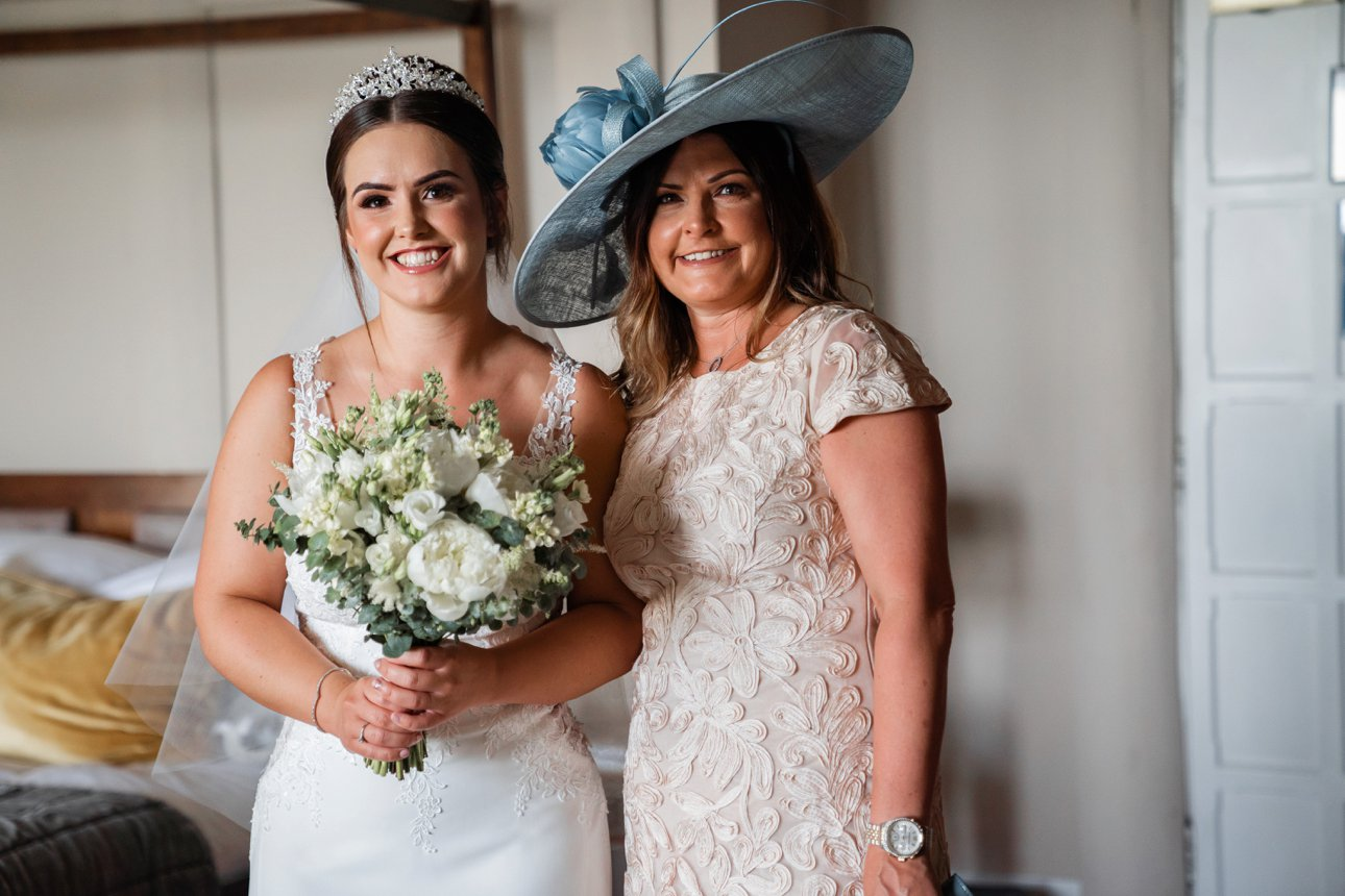 Bride Cora in her Anna Sorrano designed-bridal gown and her Fabulous Floristry by Cara white bouquet stands with her mum wearing a large blue straw hat.