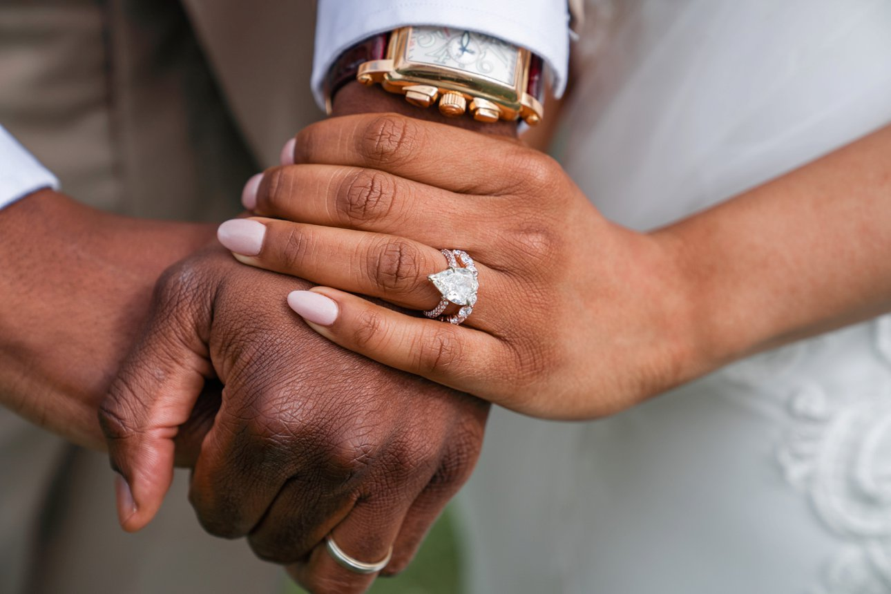 Bride has teardrop engagement ring and diamond-studded wedding band and is holding hands with the groom wearing his wedding ring.