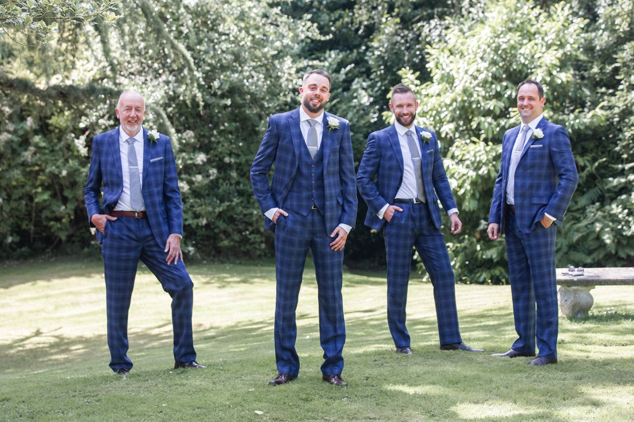 The groom, his best man and two ushers wear blue checked suits and grey ties for their wedding duties.