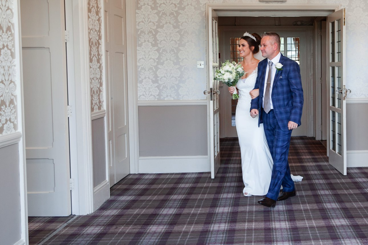 Bride Cora walks into her marriage ceremony across checked carpet at Hertfordshire wedding venue The Manor Elstree - A Laura Ashley Hotel.
