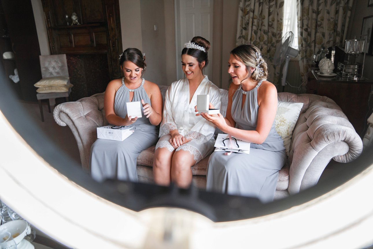 Bridesmaids in pale mauve grey dresses open a gift from the bride at Hertfordshire wedding venue The Manor Elstree - Laura Ashley hotel.