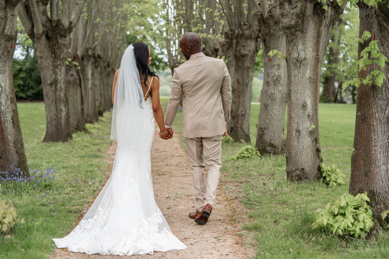 The bride and groom walk through a tree-lined avenue after their wedding at Berkshire wedding venue Coworth Park.