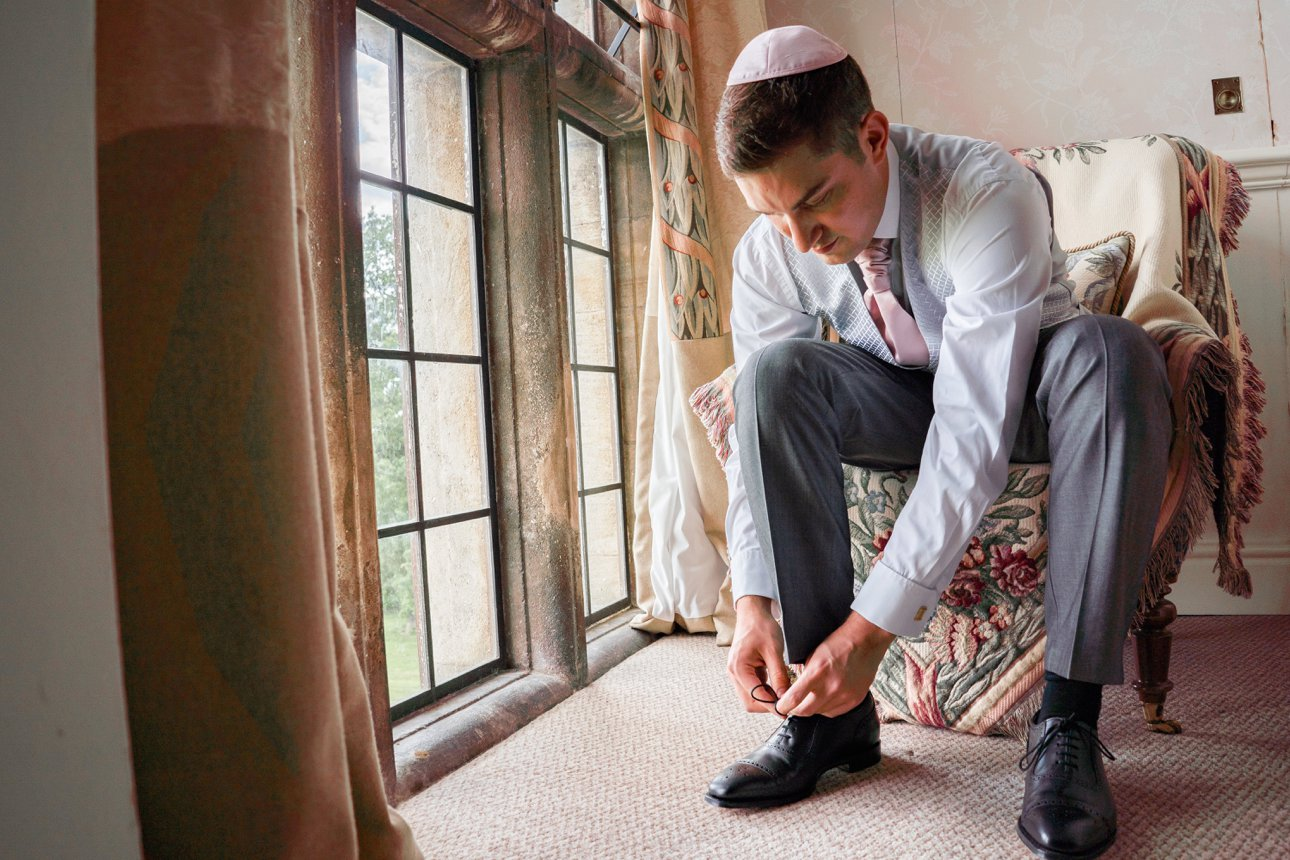 Groom puts on his shoes ready for his wedding at Stapleford Park Country House Hotel in Leicestershire.