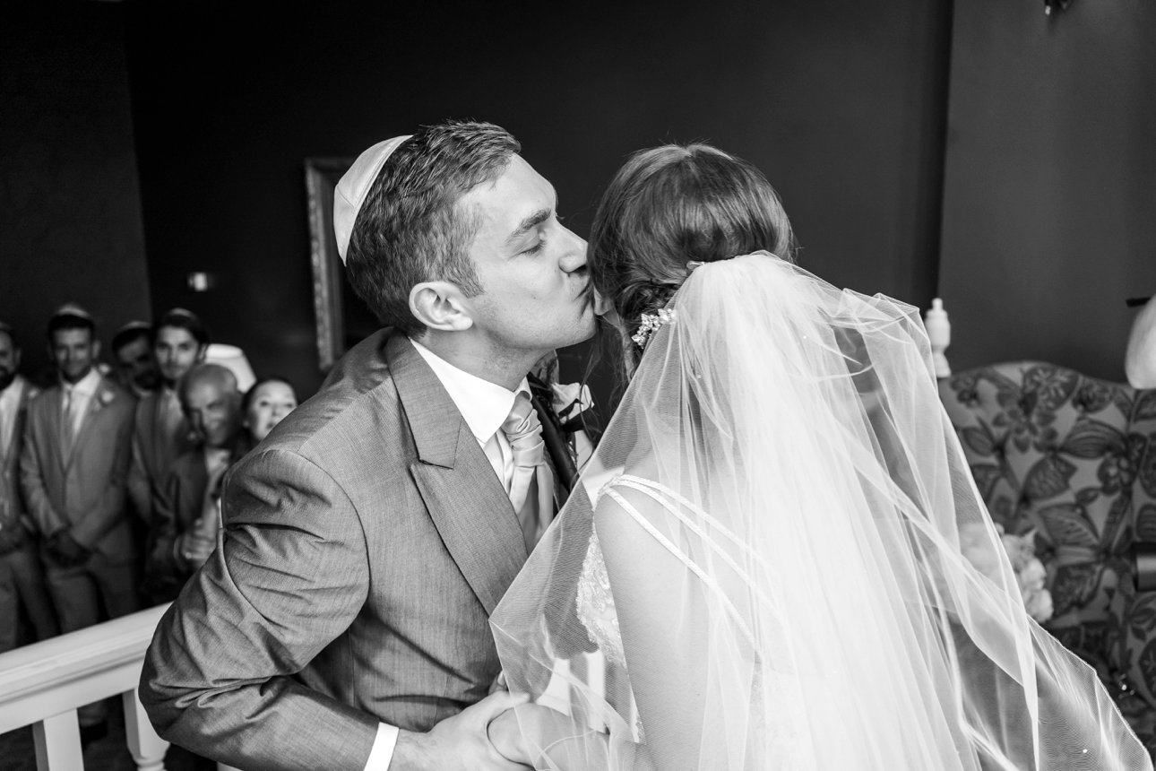 Groom Elliott kisses his bride Sonni during their badeken part of their Jewish marriage ceremony.