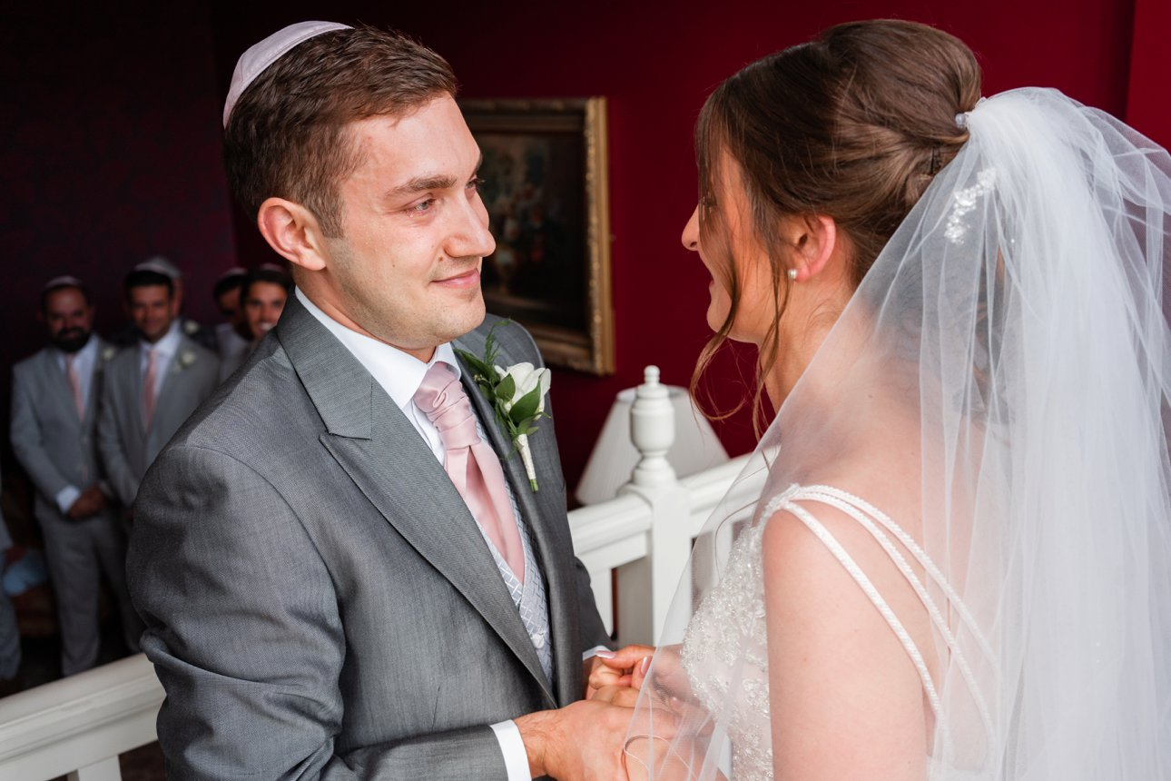 Groom Elliott and bride Sonni hold hands during their badeken part of their wedding ceremony.