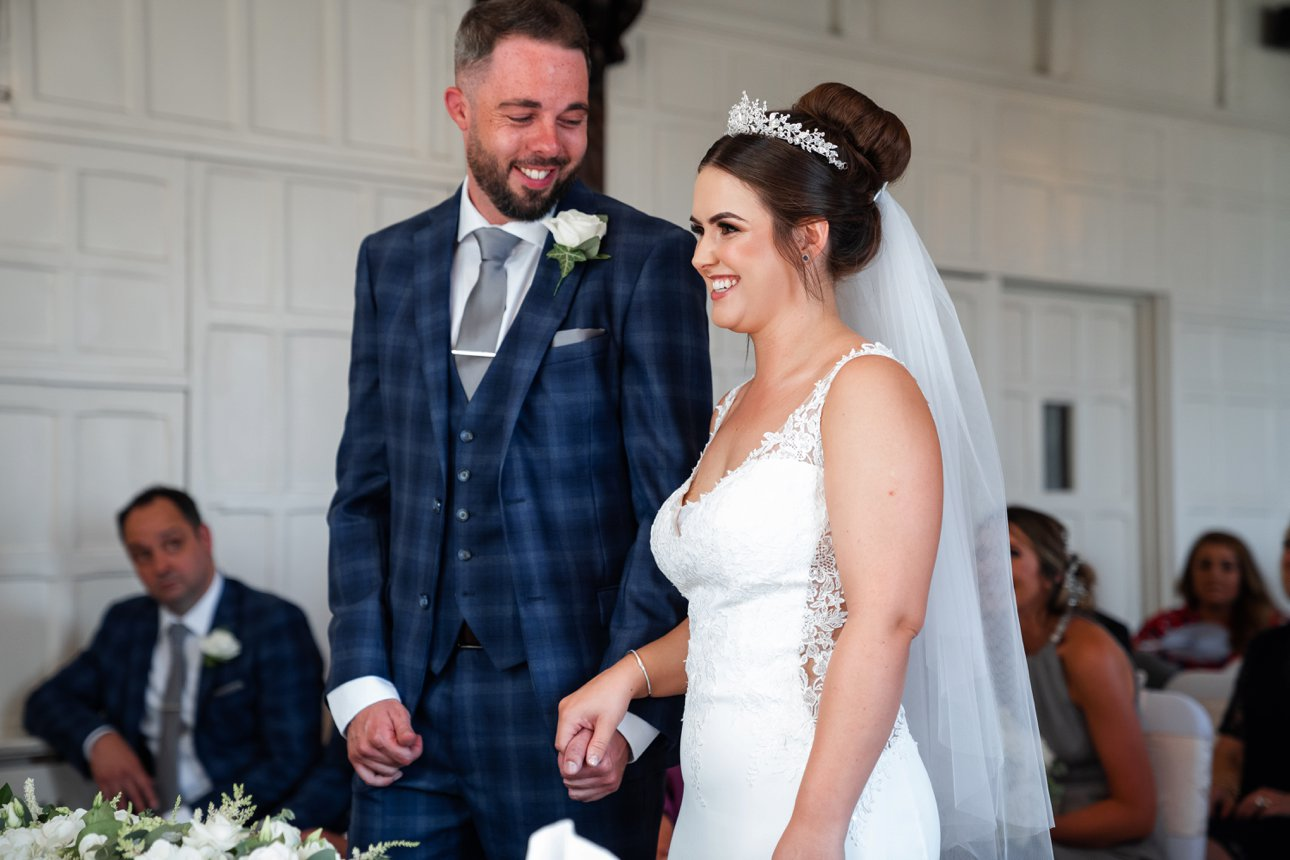 Groom Andrew and bride Cora hold hands during their marriage ceremony.