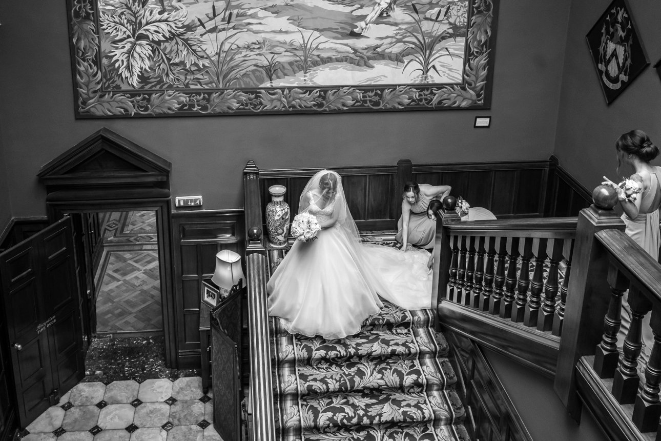 A bride and her bridesmaids descend the grand staircase at Leicestershire wedding venue Stapleford Park.