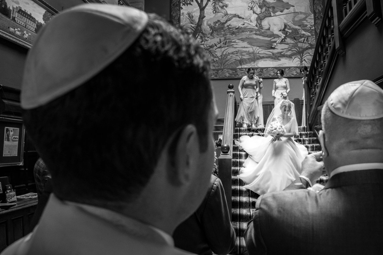 A groom and family members watch Bride Sonni descend the main staircase at Stapleford Park.