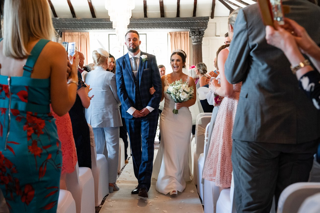 Bride and groom walk down the aisle as husband and wife after their wedding ceremony at The Manor Elstree.