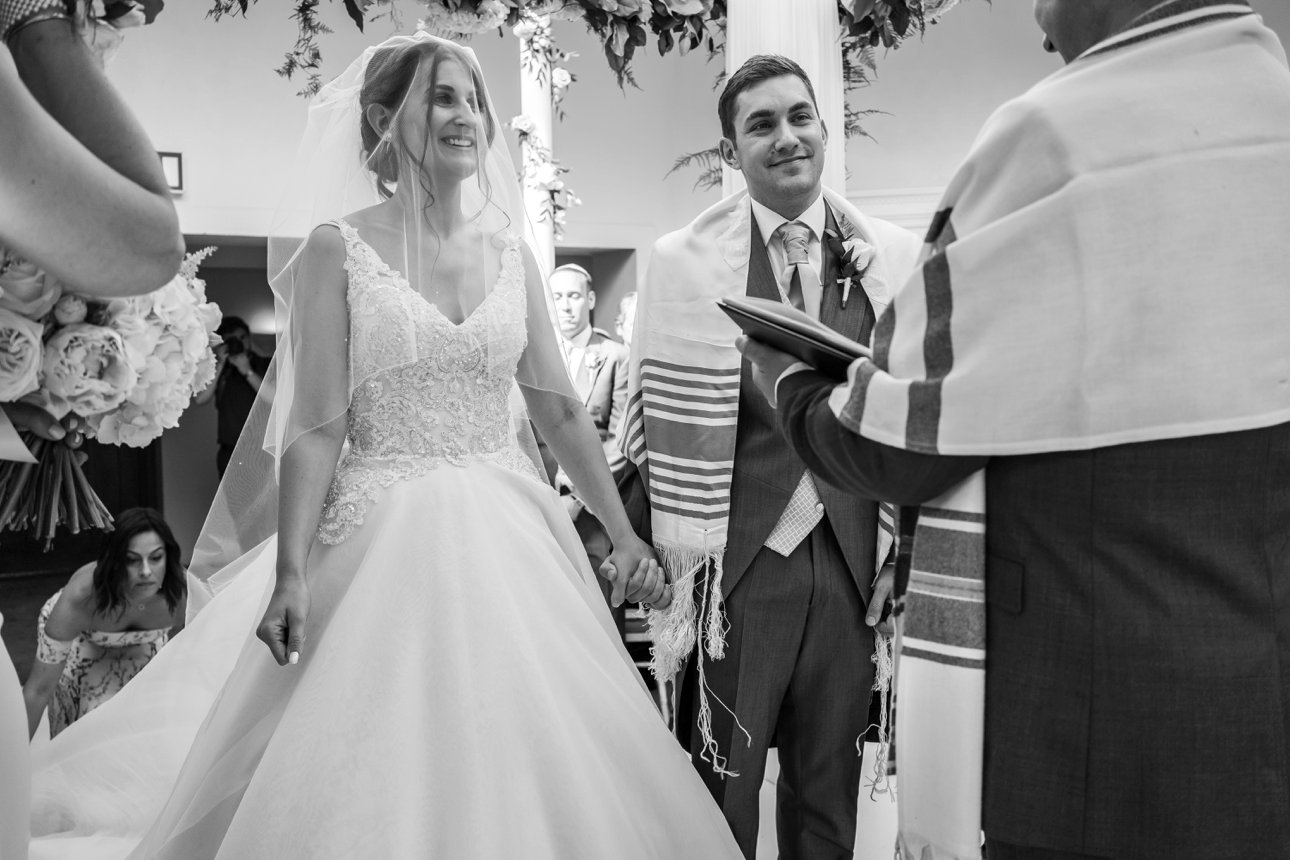 The bride and groom smile during their Jewish wedding ceremony under the chuppah at Stapleford Park.